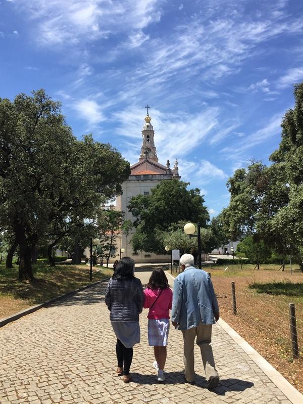한 가족이 성당을 찾았어요 이들에게 가톨릭은 종교 이상의 의미를 갖고 있는 듯 했어요. 성당으로 걸어가는 길, 할어버지, 엄마와 딸의 뒷모습이 편안하게 보였어요. 저 앞에 보이는 건물이 파티마 대성당의 종탑입니다.