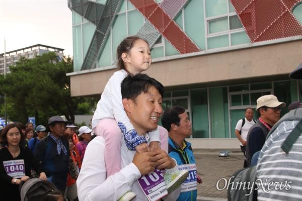 15일 진행된 평화통일염원 걷기대회에서 어린이를 무등에 태운 한 참가자가 걸음을 옮기고 있다.