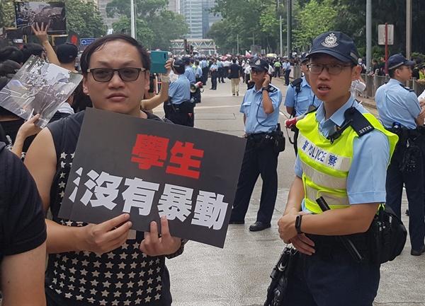 홍콩 도심에 나란히 선 '송환법 반대' 시위대와 경찰 16일(현지시간) '범죄인 인도 법안'(일명 송환법)에 반대하며 홍콩 도심을 행진하던 한 시민이 '학생은 폭도가 아니다'라는 팻말을 들고 있다. 그 옆에서 한 경찰이 이를 지켜보고 있다. 홍콩 언론은 이날 시위 참여 인원이 100만 명을 넘은 것으로 추산했다.