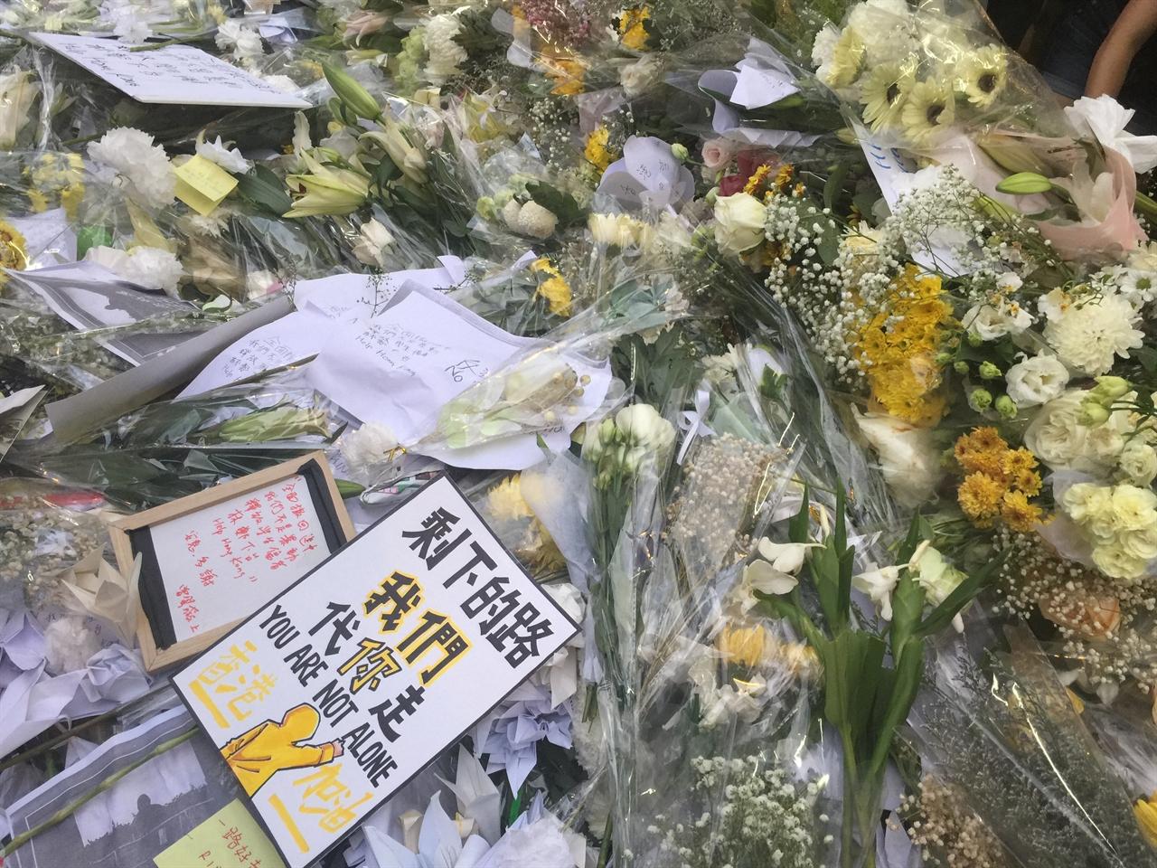 당신은 혼자가 아니다 16일 검은옷행진에서 투신 자살한 량링제씨를 추모하는 헌화 꽃 위에 놓여진 포스터 '앞으로 남은 길은 우리가 가겠다. 당신은 혼자가 아니다'