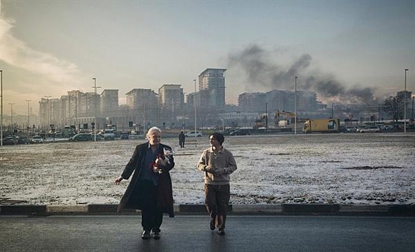 행복한 라짜로 자신이 형제의 연을 맺었다고 믿는 탄크레디와 다시 만난 라짜로. 이들의 뒤로 검은 연기를 뿜는 오염된 듯한 도시 풍경이 인상적이다.