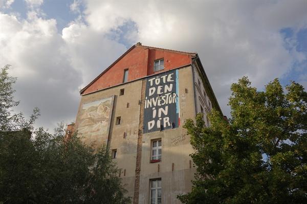 """""""너 안의 투자자를 죽여라.""""라는 문구가 써져있는 베를린의 건물벽."""