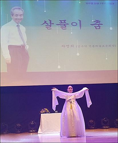 차명희 선생의 살풀이춤 김수업 선생이 환하게 웃고 있는 큰 영상 화면 밑 무대에서 차명희 선생이 고인을 기리며 살풀이춤을 추고 있다.