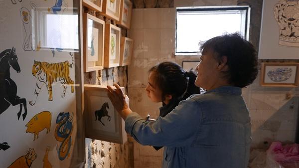 민화 만화경 프로젝트 전시 첫날.  서수아 스페이스 오매 대표와 참여 작가 김선이 님이 작품을 걸고 있다.