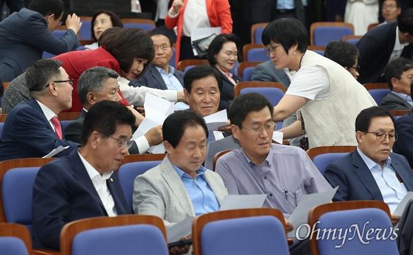 여야3당 원내대표가 국회 정상화에 최종 합의한 24일 오후 서울 여의도 국회에서 열린 자유한국당 의원총회에 참석한 의원들이 합의문을 보고 있다.