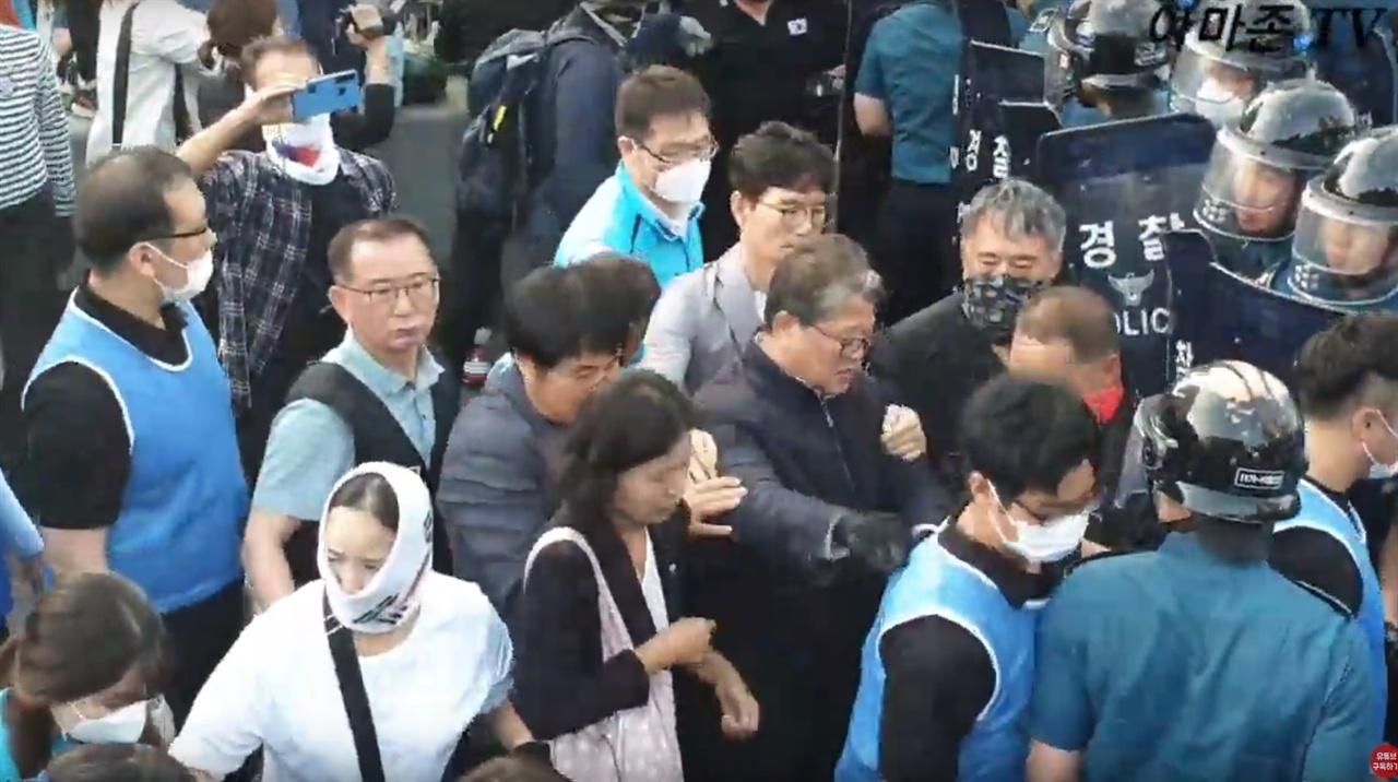 밀치는 조원진 의원 조원진 의원이 한 철거반원을 밀치자 안경 쓴 20대로 보이는 청년이 밀려나고 보좌관으로 보이는 사람이 조 의원을 두 손으로 말린다.