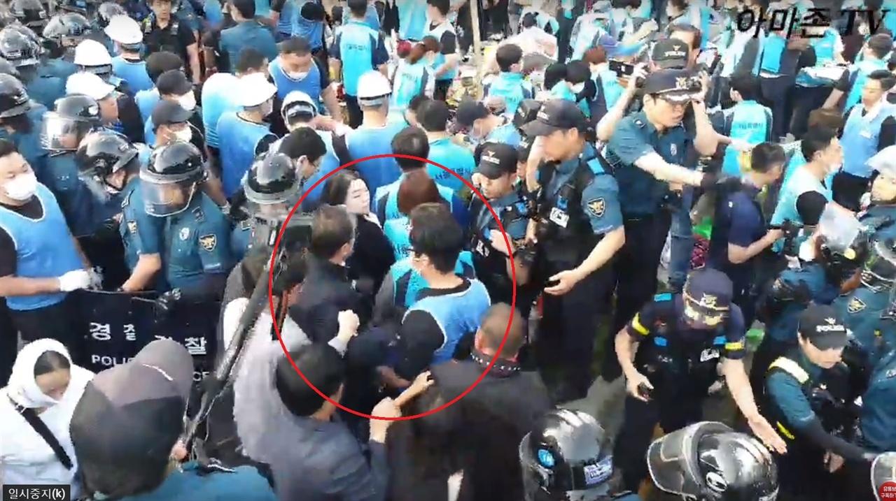 또 다시 밀치는 조원진 의원 조원진 의원은 경찰 방어막을 약간 돌아가는 동안 이 청년이 다시 보이자 그를 또 한 번 거칠게 밀었다.