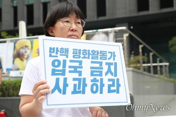 26일, AWC 한국위원회 이경자 운영위원이 서울 종로구 일본대사관 앞에서 '반색 평화활동가 입국 금지 사과하라'라는 손팻말을 들고 일본 정부에 항의했다.