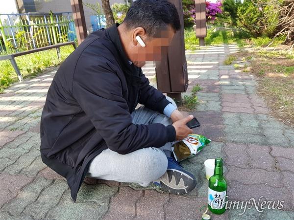 고성 산불 이재민 김(61, 남)씨가 바닥에 앉아 소주를 마시고 있다.