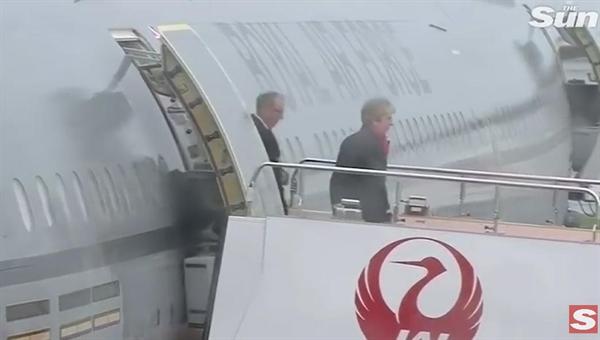 메이 영국 총리가 27일 일본 오사카 공항 도착 장면 <더 선> 영상 갈무리. 비오는 날 지붕 없는 개방형 트랩을 사용했고 우산도 쓰지 않은 채 계단을 내려왔다.