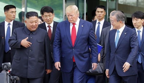 도널드 트럼프 미국 대통령, 김정은 북한 국무위원장이 30일 오후 판문점 남측 자유의 집에서 회동을 마친 뒤 문재인 대통령과 함께 군사분계선으로 이동하고 있다.