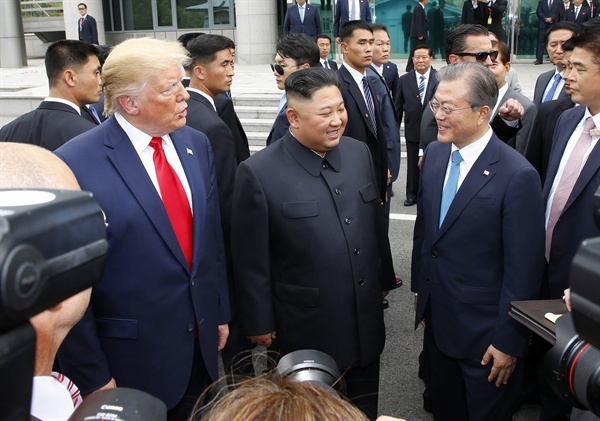 문재인 대통령(오른쪽부터), 북한 김정은 국무위원장, 미국 도널드 트럼프 대통령이 30일 오후 판문점 남측 자유의 집 앞에서 만나 얘기를 나누고 있다.