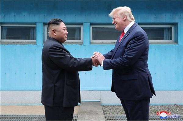 김정은 북한 국무위원장과 도널드 트럼프 미국 대통령이 6월 30일 판문점에서 만났다고 조선중앙통신이 1일 보도했다. 사진은 중앙통신이 홈페이지에 공개한 것으로, 군사분계선(MDL)을 사이에 두고 북미 정상이 손을 맞잡은 모습.