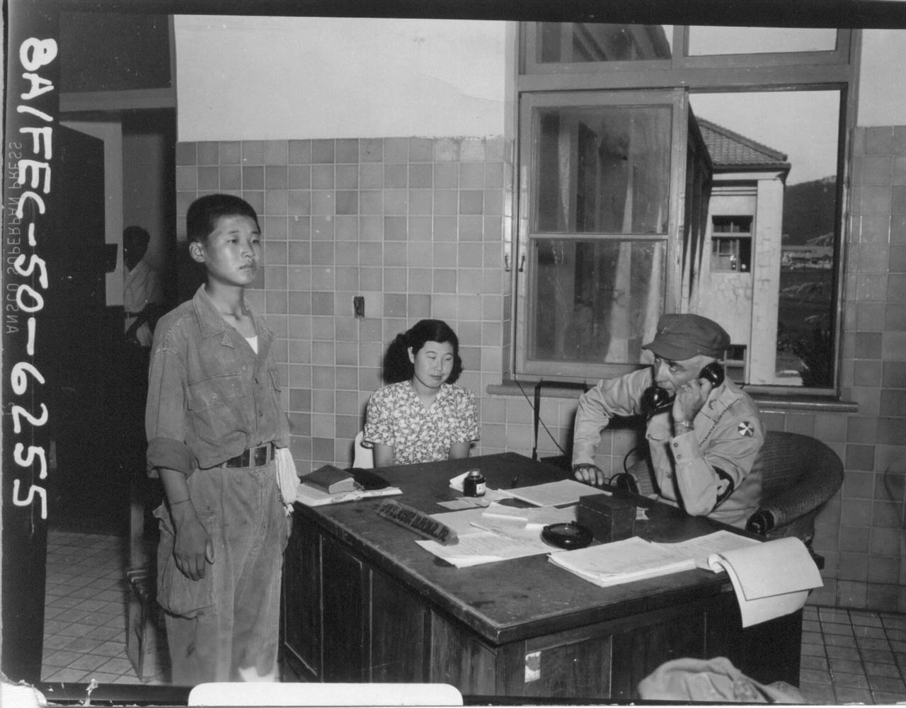 한 어린 인민군 포로가 미8군 포로신문관 앞에서 조사를 받고 있다(1950. 8. 18.).