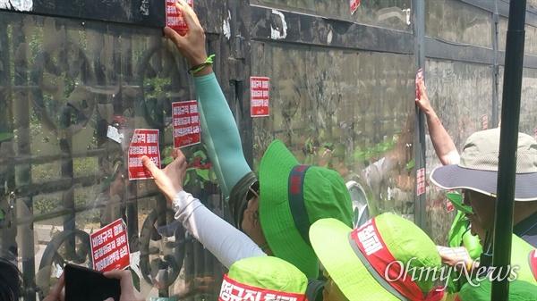 경기도교육청 정문에 스티커를 붙이는 노동자들