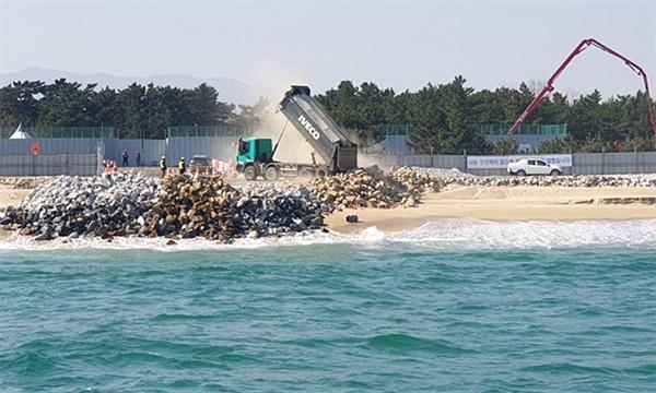 강릉 안인화력발전소 건설에서 항만 건설을 위한 매립석을 쏟아붓고 있다.