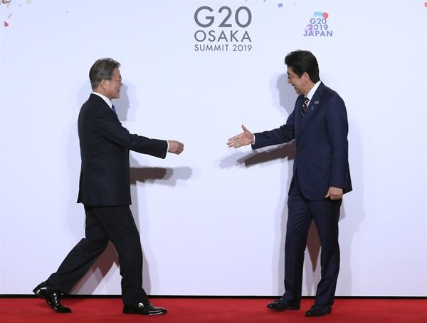 문재인 대통령이 지난 6월 28일 오전 인텍스 오사카에서 열린 G20 정상회의 공식환영식에서 의장국인 일본 아베 신조 총리와 악수하고 있는 모습.