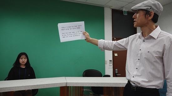 제천 행복기자학교 김문환 교수가 <단비뉴스> 스튜디오에서 수강생에게 TV뉴스 앵커 멘트를 지도하고 있다.