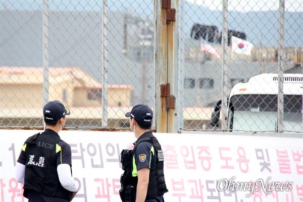 부산항 8부두에 있는 미군부대 세균무기실험실로 추정되는 시설물(태극기, 성조기 매달려 있는 건물) 앞에 경찰이 서 있다.