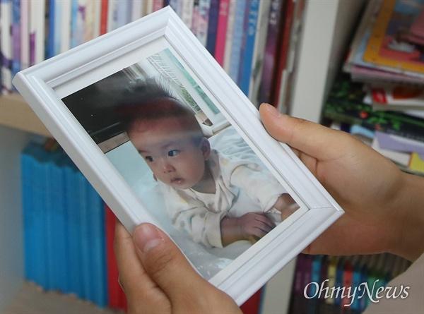 서울랜드 경사진 주차장에서 미끄러진 SUV 차량에 머리를 부딪혀 아들 잃은 고 최하준 군 어머니 고유미씨가 아들의 사진을 보고 있다.