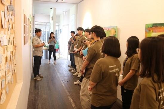 이동현 대표가 미실란 사옥 1층 복도에서 연수단에게 공간을 설명하고 있다.