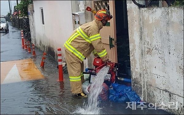 19일 오전 6시쯤 제주시 내도동의 한 주택이 침수돼 119대원들이 배수 작업을 벌이고 있다. [사진제공-제주소방서]