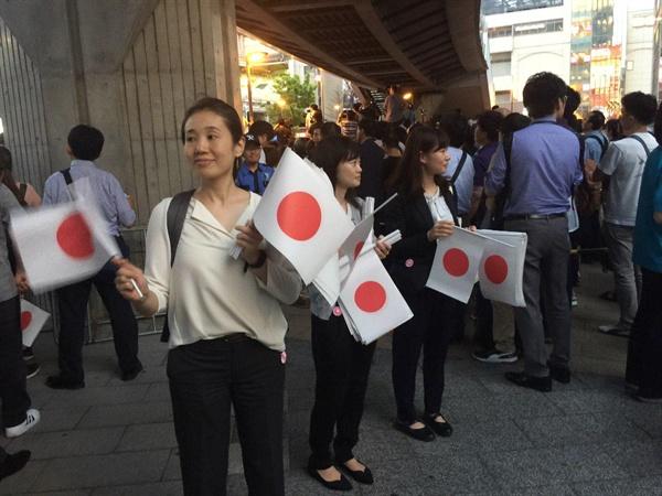 25대 참의원 선거를 하루 앞둔 도쿄시내 아카하바라역 광장에서 일장기를 나누어주는 자민당의 자원봉사자