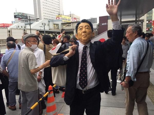 7월 21일 25대 참의원 선거 자민당 유세현장인 아키하바라역 광장에서 자민당 지지자가 아베 총리의 가면을 쓰고 지지를 호소하고 있다.