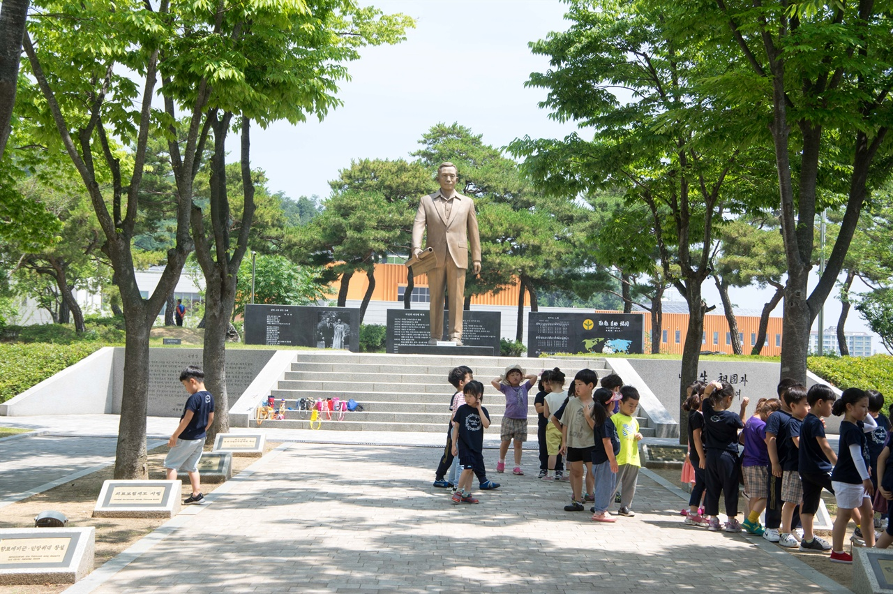 박정희 동상 앞 계단에 짐을 모아놓고 유치원 어린이들이 선생님 앞으로 모이고 있다. 이들은 박정희를 어떻게 기억하게 될까.