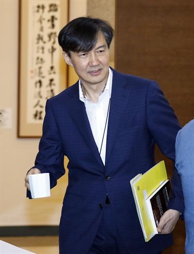 청와대 조국 민정수석이 22일 오후 청와대에서 열린 수석·보좌관회의에 입장하고 있다. 조국 수석은 이날 '일본회의의 정체'라는 책을 들고 회의에 참석했다.