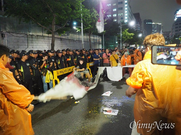 적폐청산사회대개혁 부산운동본부는 7월 27일 저녁 일본총영사관 앞에서 집회를 벌이며 아베 총리의 얼굴이 그려민 대형 펼침막에 페인트 세례를 가했다.