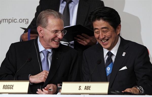 2013년 9월 7일, 아르헨티나 부에노스아이레스에서 열린 국제올림픽위원회(IOC) 제125차 총회에서 일본 도쿄가 2020년 제32회 하계올림픽 개최도시로 선정된 후 아베 신조 일본 총리(오른쪽)와 자크 로게 IOC 위원장이 개최지 선정 관련 문건에 서명한 뒤 활짝 웃고 있다.
