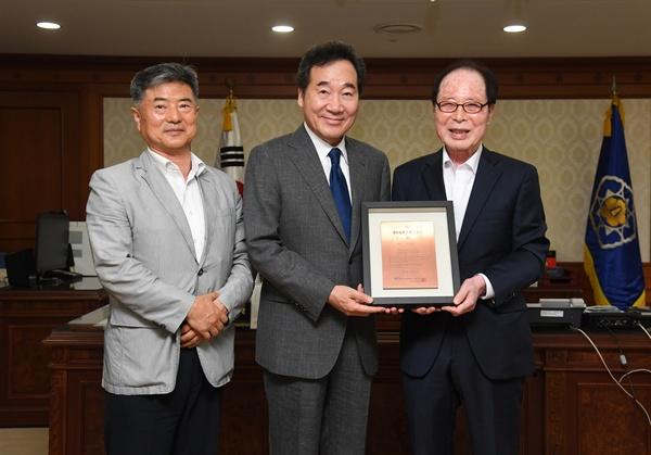 권영길 평화철도 이사장이 30일 이낙연 총리한테 '평화철도 침목 기증 인증서'를 전달했다.