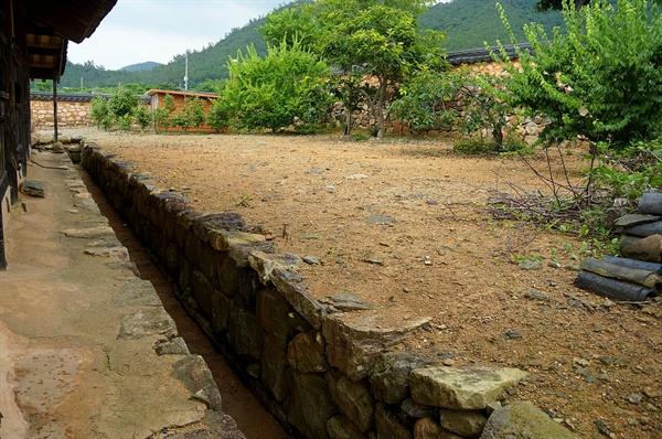 안채 뒤 토방 안채 뒤편 토방과 안채 후원 사이에 물길이 길게 나있다. 토방 기단에 굴뚝이 숨어있다. 굴뚝 연기가 나와 물길을 따라 흘러가는 모습을 상상해 본다.