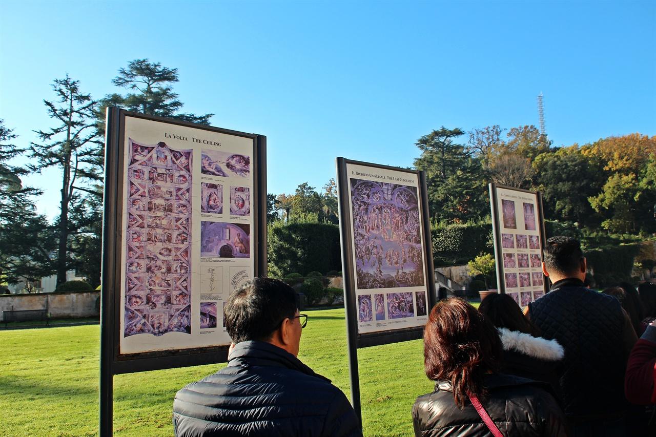 바티칸 박물관 피냐 정원에 있는 미켈란젤로의 <천지창조>와 <최후의 심판> 그림판 앞에서 작품 설명을 듣고 있는 모습