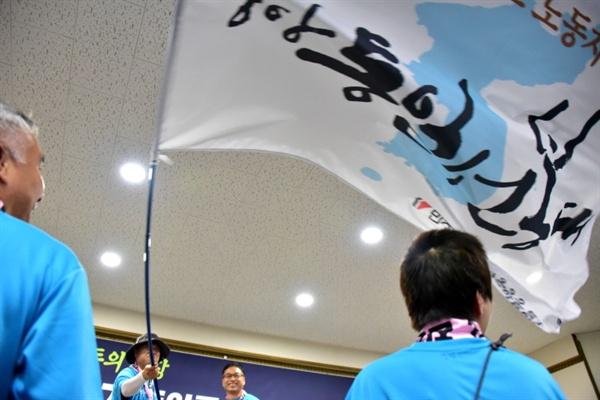 윤택근 민주노총 부위원장이 엄강민 20기 중앙통선대 대장에게 통일선봉대 깃발을 전달하고 있다.