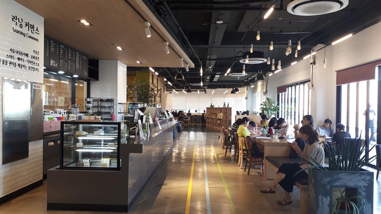 두정도서관 러닝커먼스 내부 사진 왼쪽이 러닝커먼스 내부에 있는 카페 인. 카페 인을 중심으로 양 쪽에 자유롭게 배치된 학습테이블이 있으며 상당히 넓은 편이어서 많은 사람이 이용한다.