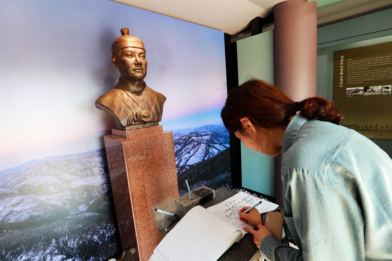 신돌석 장군 유적지를 찾은 관광객이 방명록을 작성하고 있다.