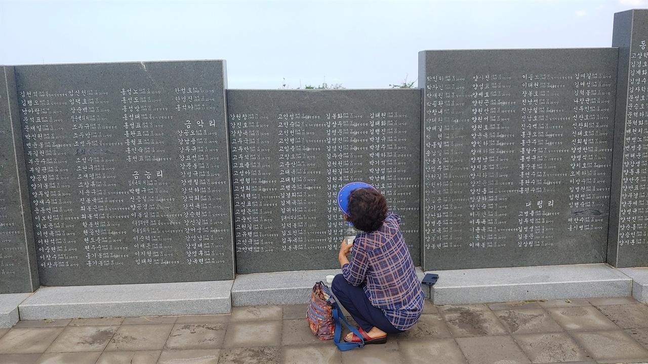 4.3 평화공원 어머니가 희생자 비석에서 외할아버지의 이름을 찾고 있다.