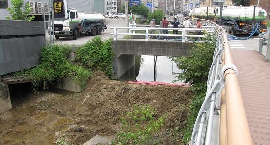 임시둑으로 하천 막고 물 퍼내는 환경미화 차량 인근 금학천으로 흘러든 암모니아 때문에 물을 퍼내고 있는 환경미화 차량