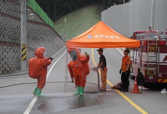 창고내부에 투입되었던 특수대응팀 창고내부에 투입되었던 특수대응팀이 오염에 노출된 특수복을 물로 씻어내고 있다.