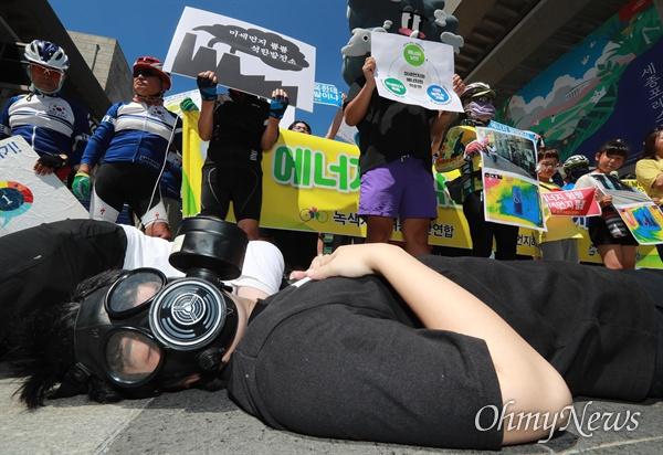 '마음껏 숨 좀 쉬자' 방독면 쓰고 쓰러진 사람들 14일 오전 서울 세종문화회관앞에서 서울환경연합, 미세먼지해결시민본부, 녹색자전거봉사단연합 회원들이 미세먼지 주요원인인 노후 석탄화력발전소 조기폐쇄와 신규 석탄화력발전소 건설 중단을 촉구했다. 일부 참가자들은 방독면을 쓰고 쓰러져, 여름철 대표적인 에너지 낭비 사례인 개문냉방(문을 열고 영업)과 석탄발전소로 고통받는 시민들을 표현하는 퍼포먼스를 벌였다.