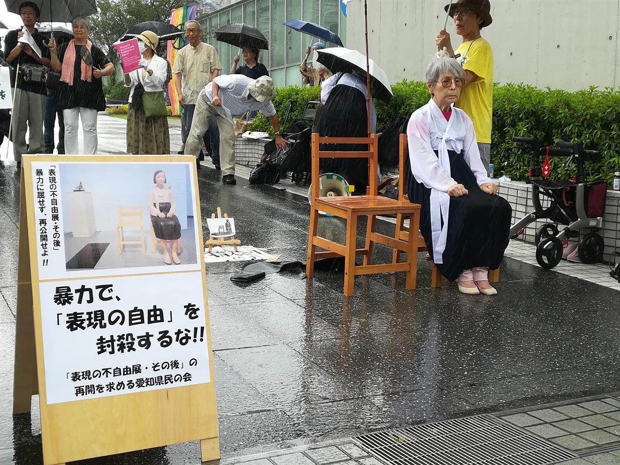 갑자기 쏟아진 폭우에도 '소녀상'의 자리를 지키는 니시 에이코씨.