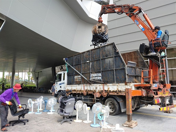 건설폐기물 업자가 선풍기 등을 수거해 적재함에 싣고 있습니다.