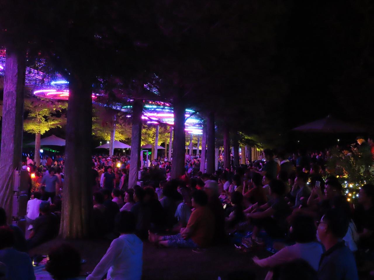 시민들의 모습 뮤직 페스티벌 공연에 역대 최고 방문객이 오면서, 행사장인 잔디광장에 가지 못한 시민들이 장미정원 인근 대로에서 전광판을 통해 공연을 구경하고 있다.