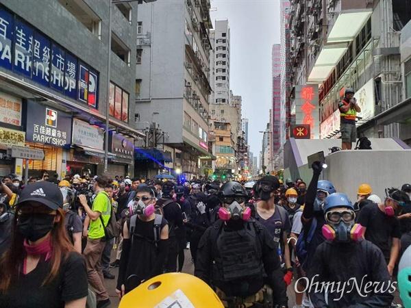 진압경찰과 대치중인 홍콩시민들 17일 오후 송환법 반대와 경찰 과잉진압을 규탄하는 행진을 하던 홍콩시민들이 몽콕경찰서앞에서 진압경찰과 대치하고 있다. 일부 시민들은 헬멧, 보안경, 방독면을 착용하고 있다.