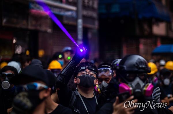 17일 오후 홍콩 몽콕 경찰서 주변에서 송환법 반대 시위 참가자들이 경찰과 대치하던 중 충돌에 대한 대비를 하고 있다.