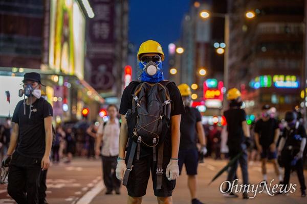 7일 오후 홍콩 몽콕 경찰서 주변에서 송환법 반대 시위 참가자들이 경찰과 대치하던 중 최루탄에 대비해 방독면을 쓰고 있다.