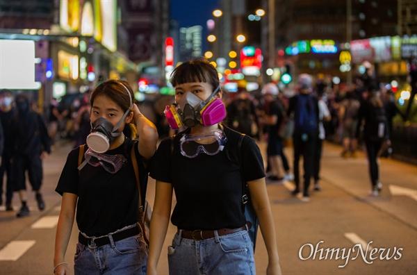 17일 오후 홍콩 몽콕 경찰서 주변에서 송환법 반대 시위 참가자들이 경찰과 대치하던 중 최루탄에 대비해 방독면을 쓰고 있다.