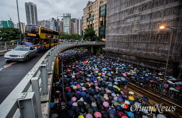 중국 정부의 강경진압 경고에도 불구하고 18일 오후 송환법에 반대하는 홍콩시민들이 빅토리아 공원을 가득 채워 집회를 성사시킨 뒤, 폭우 속에 거리행진을 하고 있다.